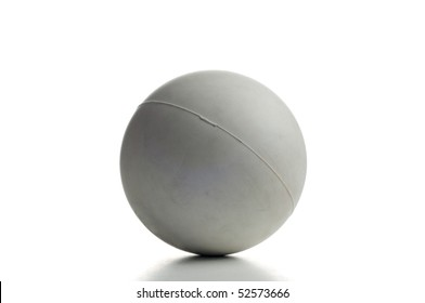A gray lacrosse ball over white with small shadow