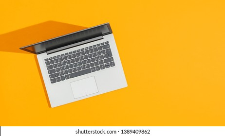 Gray laptop on a bright yellow desk and blank copy space, top view