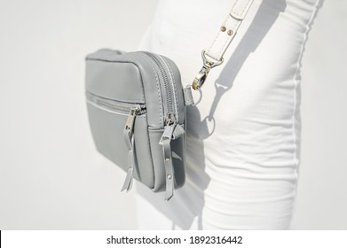 Gray Leather Crossbody Purse Leather Clutch Purse - Small Shoulder Bag. A girl in a white dress on a white background wears a trendy leather bag.