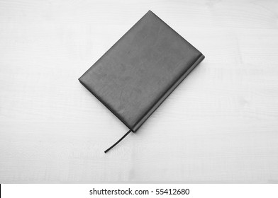 Gray leather diary book laying on wooden table