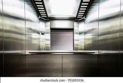 Gray metal elevator with a mirror in front of the door