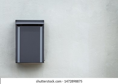 Gray metal mailbox mounted on the cement wall detail object