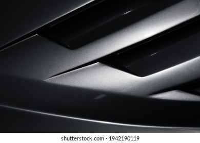 Gray metallic sports car body parts, aerodynamics grille covers air intake system, close up photo, abstract modern car design template