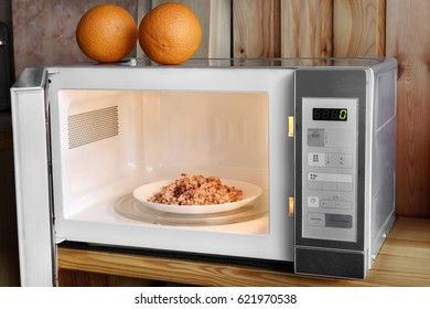 Gray microwave oven with buckwheat porridge in a white plate on a wooden background