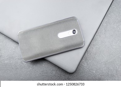 Gray mobile phone with a knitted nylon back lies on a closed textured laptop cover on a gray textural background