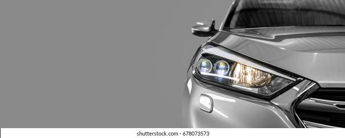 Gray modern car closeup on black background.