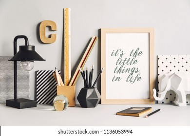 Gray modern and stylish workspace with wooden mock up poster frame, notebooks, elephant figures, table lamp and office accesories. Creative compostition of desk in gray interior.