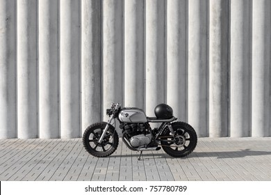 Gray motocycle in front of the wall with black helmet