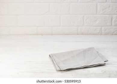 Gray napkin isolated on white wooden table. Copy space. Brick wall background. Front view.