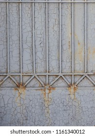 gray old painted cracked metal welded fence with vertical stripes and cracks and paint peeling off and showing rust with smudges