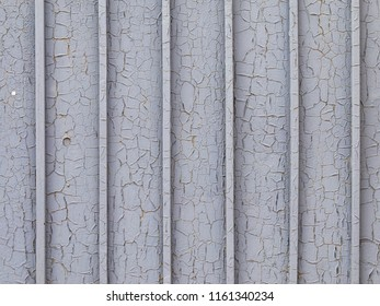 gray old painted cracked metal fence with vertical stripes and cracks and paint peeling off and rusting through
