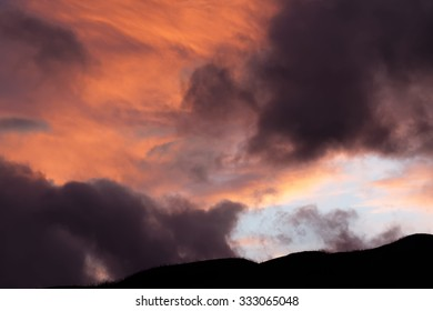 gray and orange fragmented clouds against mountaintop silhouette