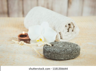 Gray oval pumice stone with natural string, brown tea candle burning, beige rolled towel and white orchid blossom on the background on natural wooden background. Feet care concept.