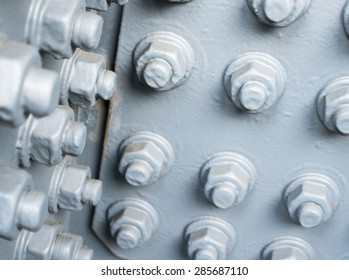 Gray painted metal surface with bolts and hexagon nuts.