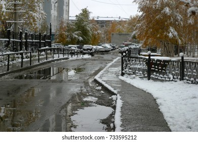 Gray pavement and road with puddles and snow, trees with yellow leaves, a courtyard with parked cars. The first snow in the autumn, in October. Autumn and winter background