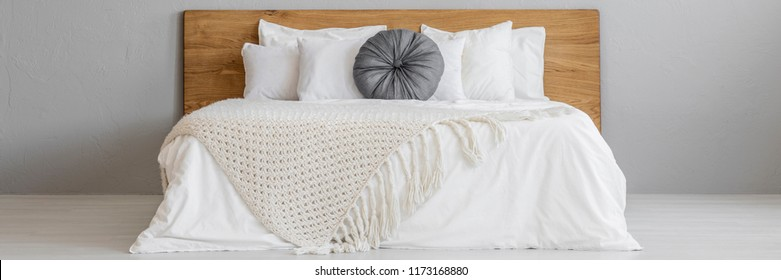 Gray pillow and beige blanket on a simple bed with white sheets and wooden headboard in a minimal, empty bedroom interior with gray walls. Place for your nightstand