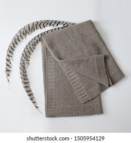 Gray plaid made of natural cotton lies on the table. Above him are the gray feathers of a pheasant.