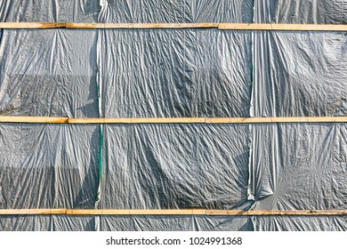 gray plastic cloth cover of building under construction at construction site for protection