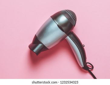 Gray plastic hair dryer on a pink pastel background. Hair care.