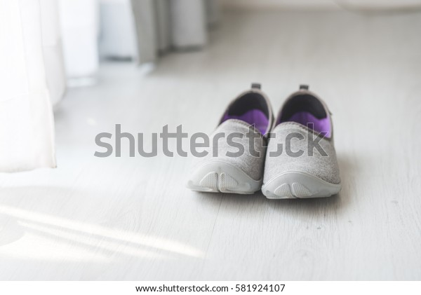 Gray, purple fabric shoes  beside view for walking on wooden gray floor