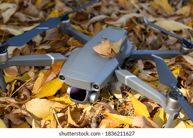 Gray quadcopter in the park on yellow autumn leaves