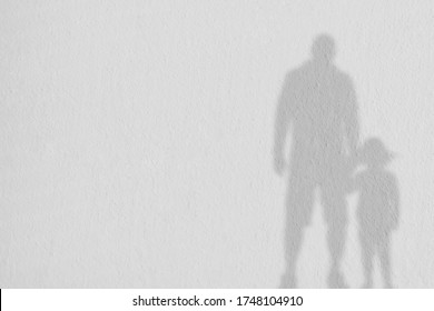 Gray shadow of the Cute boy with dad on a white wall. Abstract Father's day concept background. Space for text.