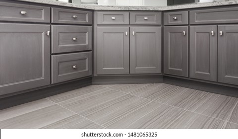 gray shaker style kitchen / vanity / bathroom cabinet with chrome color rectangular handles, porcelain floor tiles