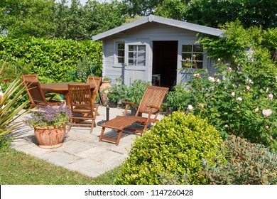 Gray shed with terrace and wooden garden furniture