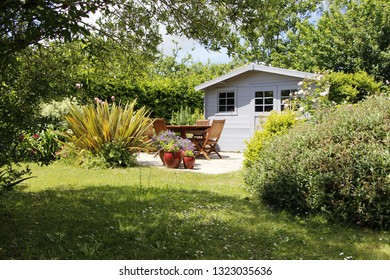 Gray shed with terrace and wooden garden furniture during spring