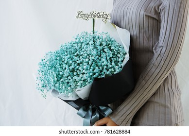 Gray shirt women are embracing bouquet of blue gypsophila, baby's breath flowers, whith dark blue paper and happy birthday wood stick