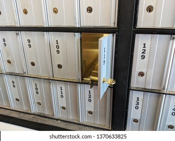 Gray Silver Metal Numbered PO Box Mailboxes at the Post Office in a Grid with Keyholes and One Open Door Empty with a Key Sticking Out