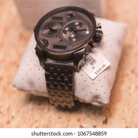 """Gray or silver metal watch wrapped around cushion with price tag reading """"$350.00"""""""
