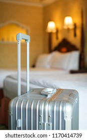 The gray silver travel suitcase is in an unoccupied hotel room and there is white linen cover