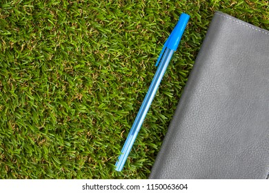 Gray sketchpad with pen on on the green artificial grass