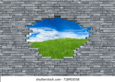 gray slate stone rock wall with breakthrough hole breakout freedom concept in front of green meadow with blue sky background