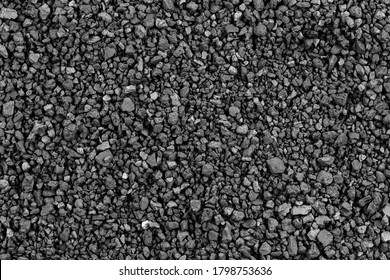 Gray small rocks ground texture. black small road stone background. gravel pebbles stone seamless texture. dark background of crushed granite gravel, close up. clumping clay