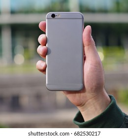 Gray smart phone in a man's hand back view on a blurry city background. Template of phone case