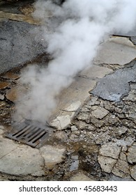 gray smoke rising from a sewer's rain drain at old street in Sarajevo, Bosnia