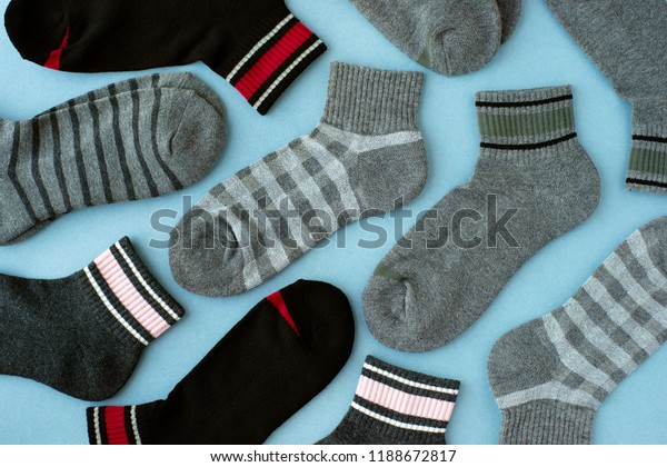 Gray socks on a blue background. View from above. Warm clothing for the feet in the form of socks. Many socks are scattered on the table.