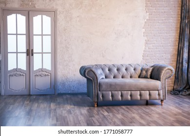Gray sofa chester on a background of gray wall in classic livingroom