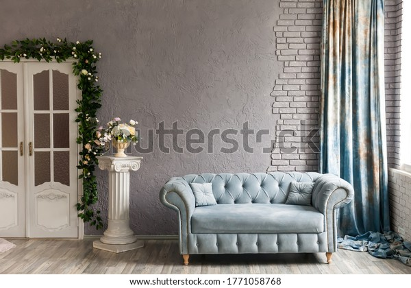 Gray sofa chester on a background of gray wall in classic livingroom with column, vintage doors and flowers