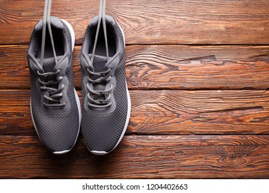 Gray sport shoes on wooden wall background