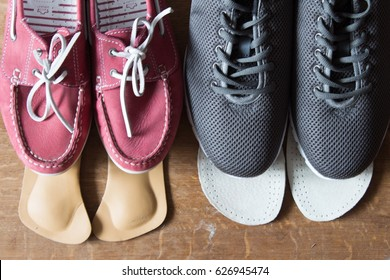 Gray sport shoes and pink sneakers with orthopedic insoles. Wooden background.