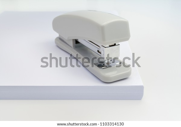 gray stapler is located on a pile of white paper, close-up abstract chancery background