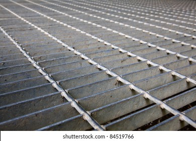Gray steel grating image taken low to the ground for a long diminished perspective