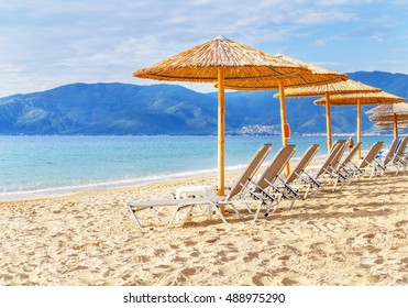 Gray straw umbrella on beautiful beach and ocean and sky