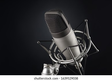 Gray studio condenser microphone in shock mount on black background