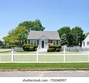 Gray Suburban Bungalow Home White Picket Fence Blue Sky USA