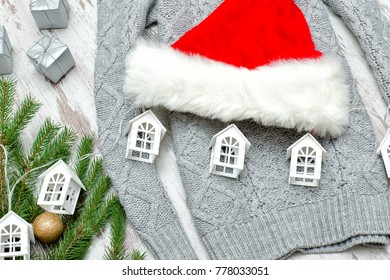 Gray sweater, Santa's hat and fir branch. Gifts and small houses