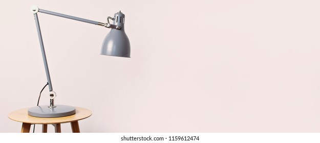 A gray table lamp in the interior against a white wall. The concept of business or education with a place for your text. Detail of interior, minimalism background. Pink toned effect.